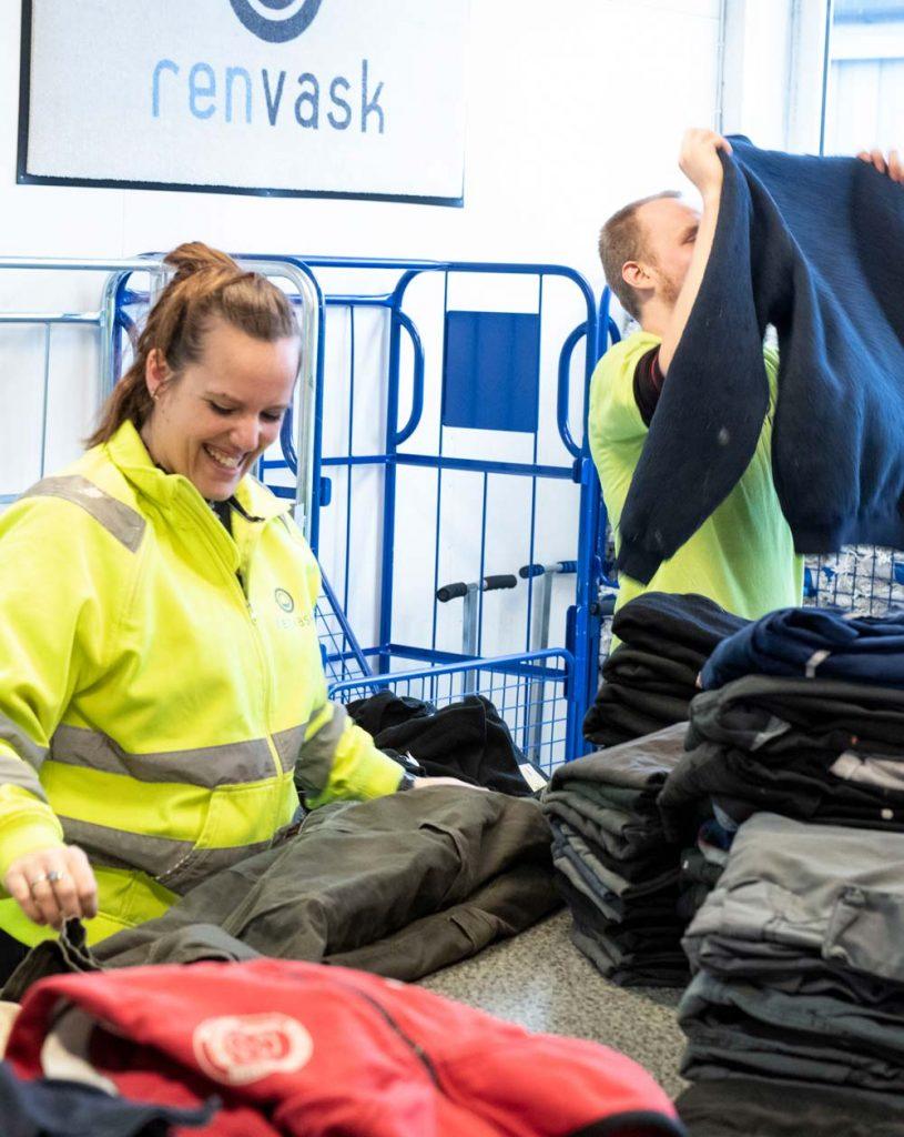 To ansatte hos Ren Vask inspiserer og brette arbeidstøy etter vask.